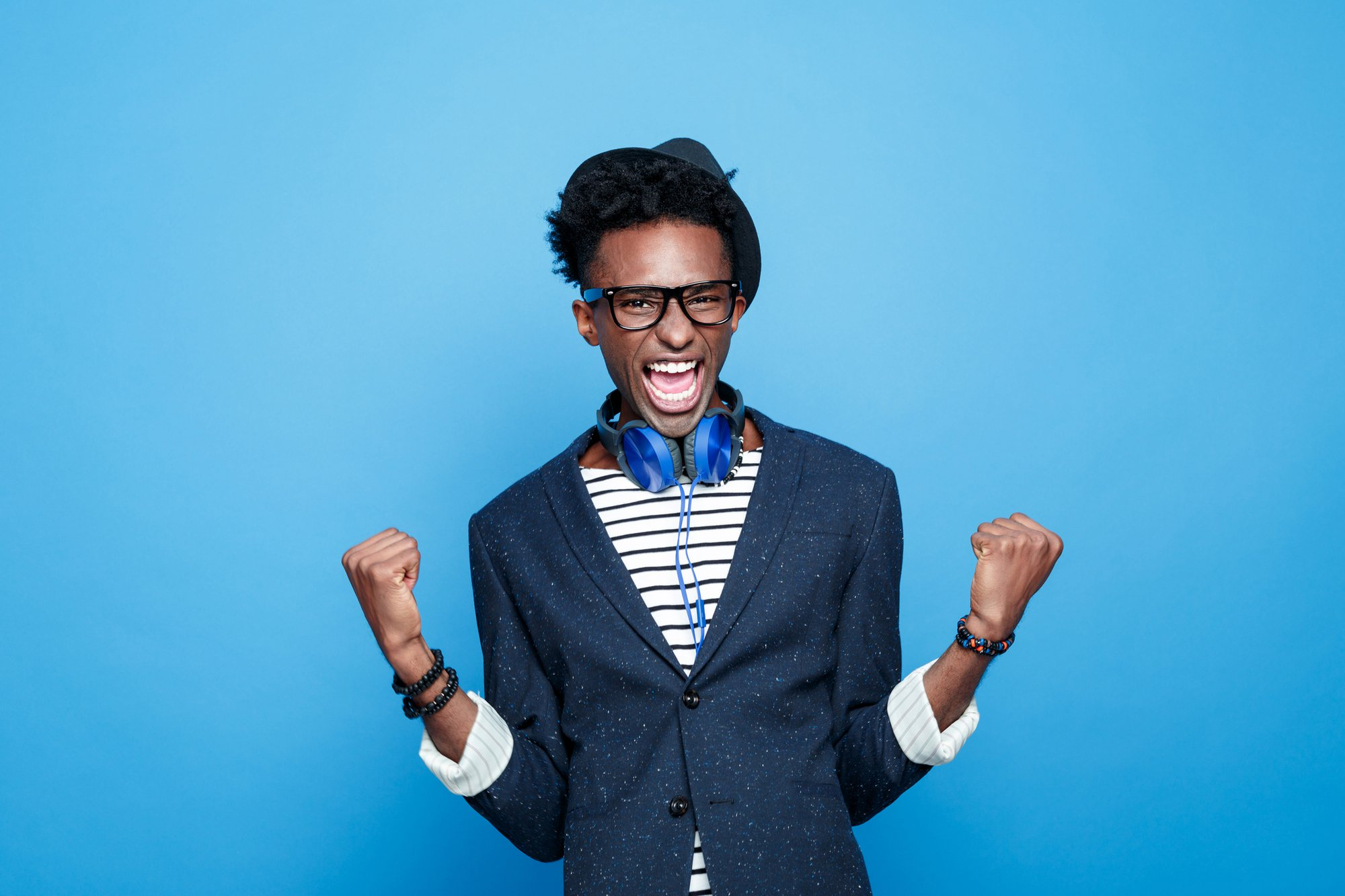 Studio portrait of successful afro american young man wearing striped top, navy blue jacket, nerd glasses, hat and headphone, laughing at camera with raised fists. Studio portrait, blue background.